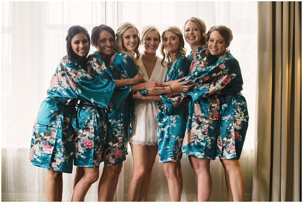 Bride in white satin robe poses with bridesmaids in blue satin robes with pink floral pattern, Axis Pioneer Square wedding, Seattle wedding, Perfectly Posh Events, Seattle Wedding Planner, Photo by Roland Hale
