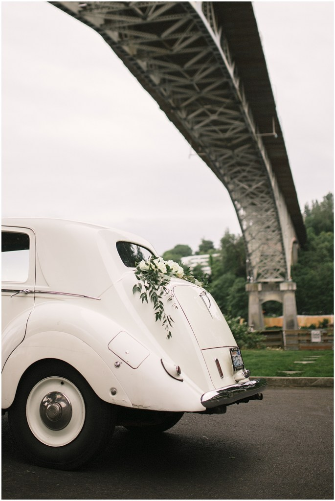 White vintage car decorated with white flowers and greenery parked under Seattle