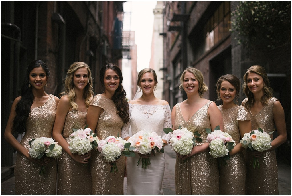 Bride poses with bridesmaids in gold sequined gowns while holding ivory and blush bouquets, Axis Pioneer Square wedding, Seattle wedding, Perfectly Posh Events, Seattle Wedding Planner, Photo by Roland Hale