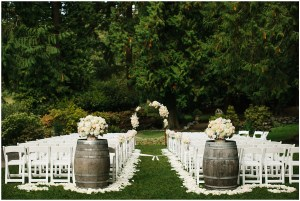 Wedding ceremony site featuring ivory and blush floral bouquets atop a wine barrels, white folding chairs and an ivory and blush floral altar, Seattle wedding, Perfectly Posh Events wedding planning and design, Seattle and Portland Wedding Planner, Photo by Lucid Captures Photography