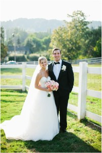 Groom poses in front of white fence with bride in white tulle ballgown while holding white and blush bouquet, Woodinville wedding at DeLille Cellars, Seattle wedding, Perfectly Posh Events wedding planning and design, Seattle and Portland Wedding Planner, Photo by Lucid Captures Photography