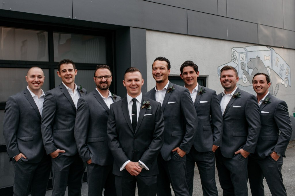 Groom and groomsmen wearing grey suits pose outside, Fremont Foundry wedding, Seattle wedding, wedding planning and design by Perfectly Posh Events, Seattle Wedding Planner, Photo by Brittney Hyatt