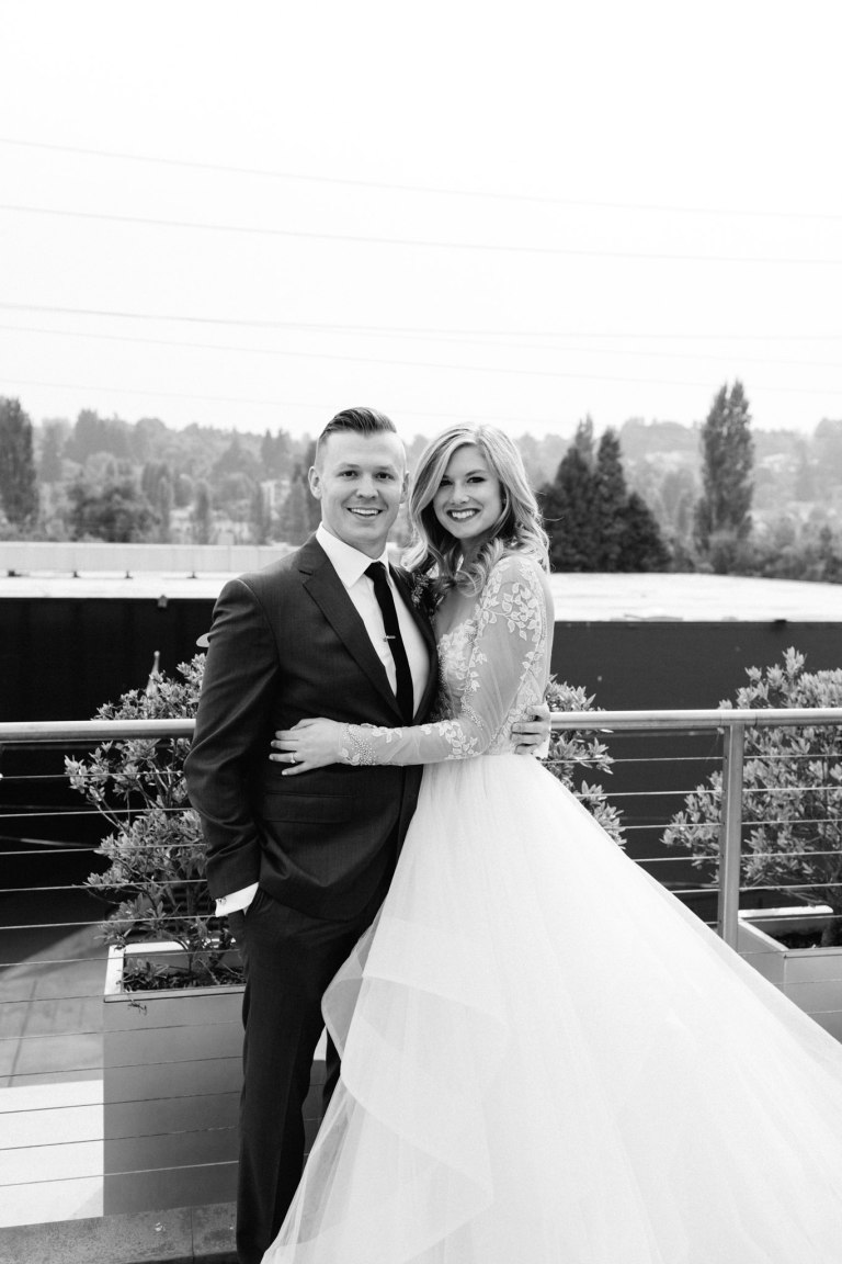 Bride and groom pose together on rooftop with Seattle