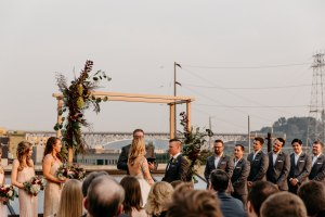 Bride and groom exchange their vows in front of guests on rooftop with view of Seattle's Fremont neighborhood in background, Fremont Foundry wedding, Seattle wedding, wedding planning and design by Perfectly Posh Events, Seattle Wedding Planner, Photo by Brittney Hyatt