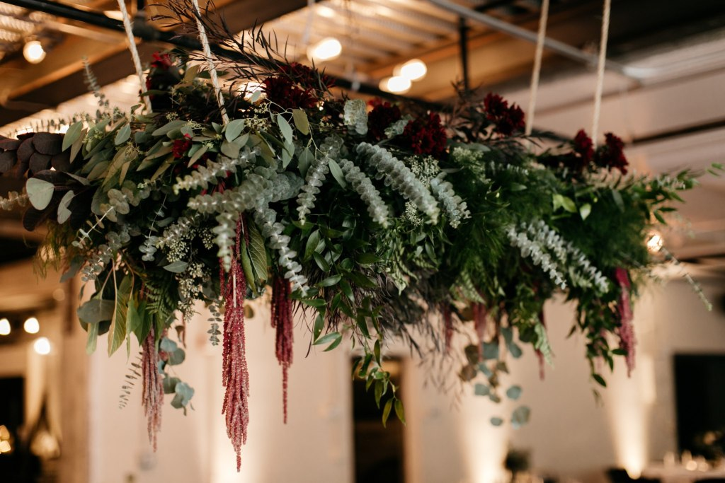 Burgundy and dark green floral display hung from ceiling in industrial event space, Fremont Foundry wedding, Seattle wedding, wedding planning and design by Perfectly Posh Events, Seattle Wedding Planner, Photo by Brittney Hyatt