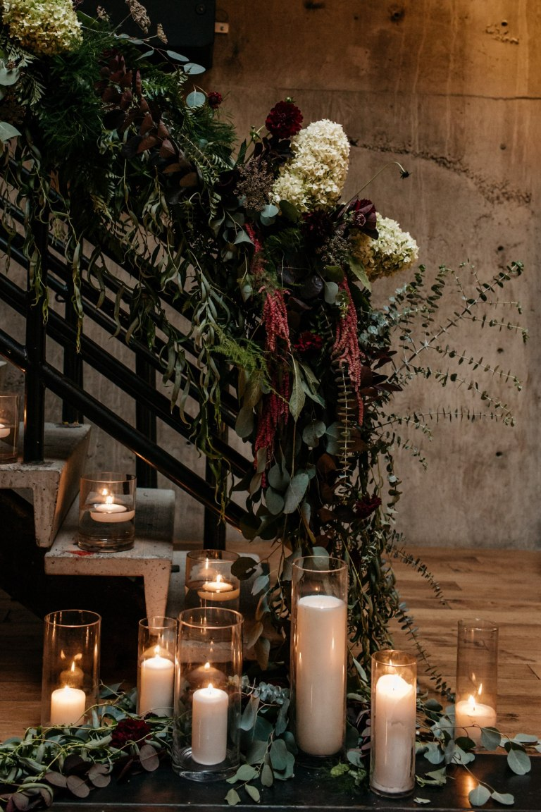 Industrial staircase decorated with florals and greenery featuring a large pillar candle display on floor, Fremont Foundry wedding, Seattle wedding, wedding planning and design by Perfectly Posh Events, Seattle Wedding Planner, Photo by Brittney Hyatt
