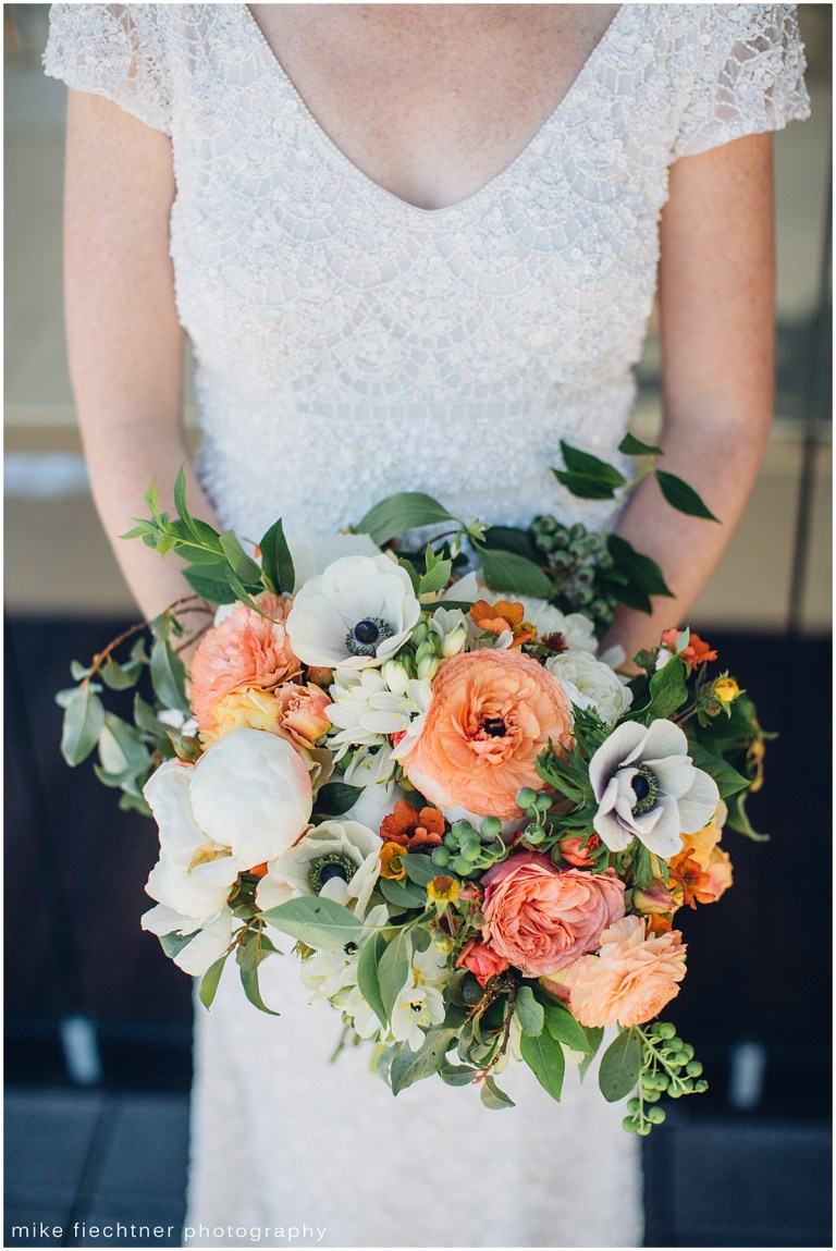 Bride in ivory lace gown holding bouquet featuring white and coral flowers and touches of greenery, Olympic Rooftop wedding, Seattle wedding, wedding planning by Perfectly Posh Events, Seattle and Portland Wedding Planner, Photo by Mike Fiechtner Photography