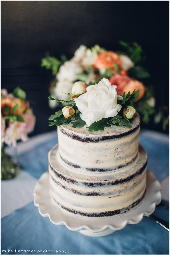 Two tier chocolate wedding cake featuring white naked frosting and decorated with white flowers, Olympic Rooftop wedding, Seattle wedding, wedding planning by Perfectly Posh Events, Seattle and Portland Wedding Planner, Photo by Mike Fiechtner Photography