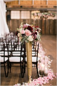 Burgundy, white, and blush floral bouquet in tall gold vase framing wedding aisle, Seattle wedding at Sodo Park, Perfectly Posh Events wedding planning and design, Seattle and Portland Wedding Planner, Photo by Kimberly Kay Photography