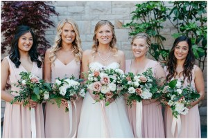 Bride poses with bridesmaids in blush colored gowns hold white and blush floral bouquets, Sodo Park wedding, Seattle wedding, Perfectly Posh Events wedding planning and design, Seattle and Portland Wedding Planner, Photo by Kate Price Photography
