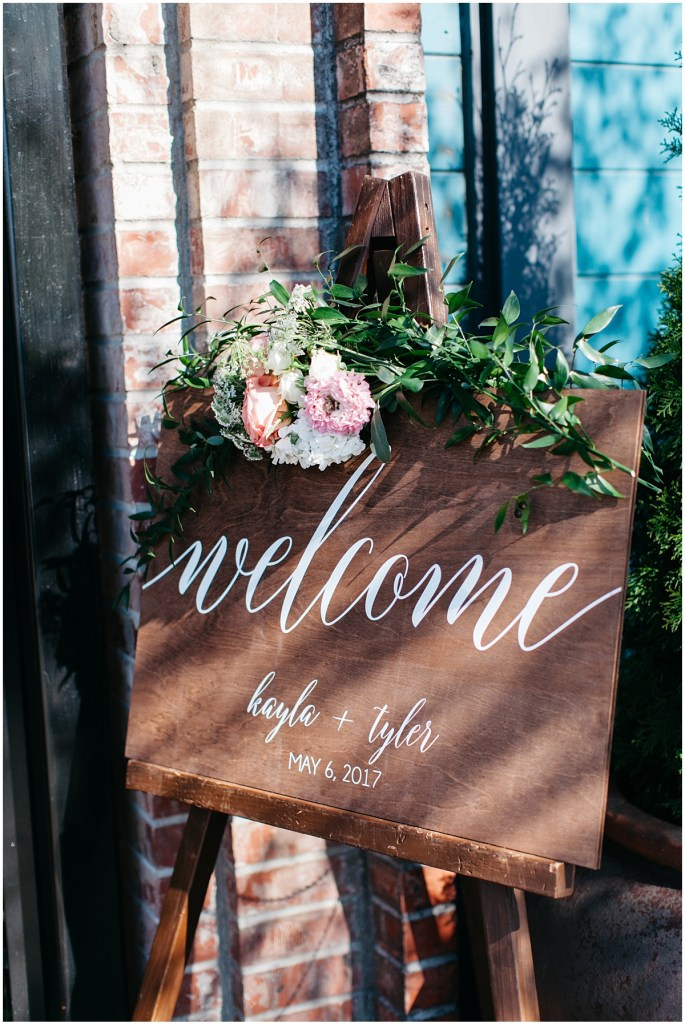 Rustic wood welcome sign with hand painted calligraphy with touches of greenery and florals, Sodo Park wedding, Seattle wedding, Perfectly Posh Events wedding planning and design, Seattle and Portland Wedding Planner, Photo by Kate Price Photography