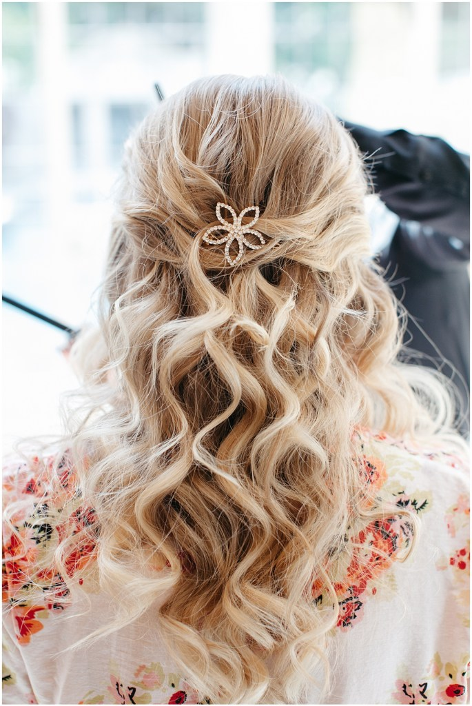Bridal hair style featuring a half-up style with curled hair and accessorized with a flower-shaped hair clip, Sodo Park wedding, Seattle wedding, Perfectly Posh Events wedding planning and design, Seattle and Portland Wedding Planner, Photo by Kate Price Photography