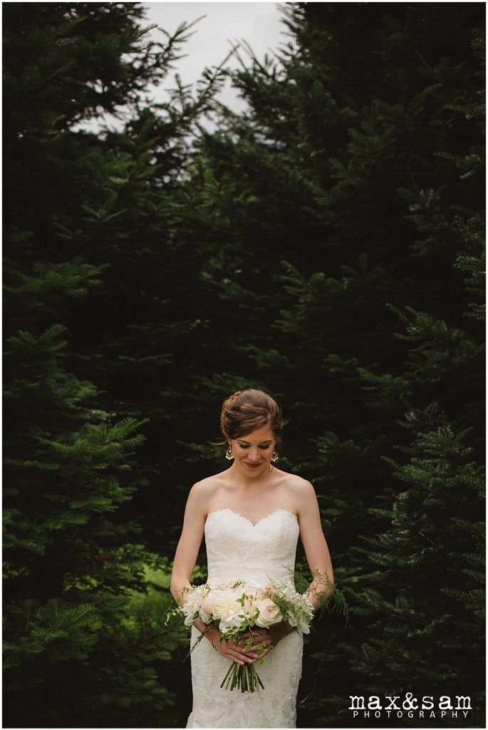 Bride poses in front of pine trees while holding an ivory and blush colored flower bouquet, The Lodge at Fall City wedding, Seattle wedding, planning and design by Perfectly Posh Events, Seattle Wedding Planner, Photo by Max & Sam Photography