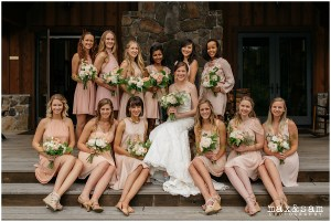 Bride poses with bridesmaids in blush toned gowns while holding ivory and blush floral bouquets, The Lodge at Fall City wedding, Seattle wedding, planning and design by Perfectly Posh Events, Seattle Wedding Planner, Photo by Max & Sam Photography