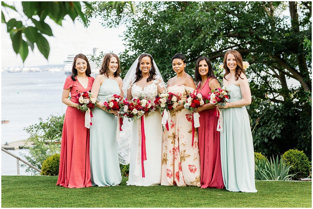 Bride poses outside with bridesmaids wearing red and mint colored gowns, Admiral