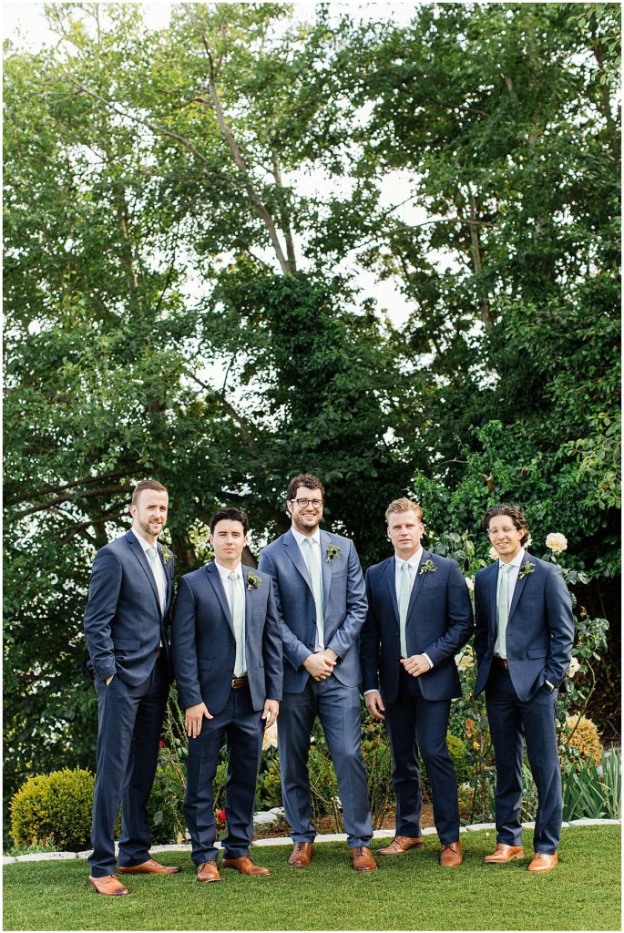 Groom poses outside with groomsmen in blue suits, Admiral