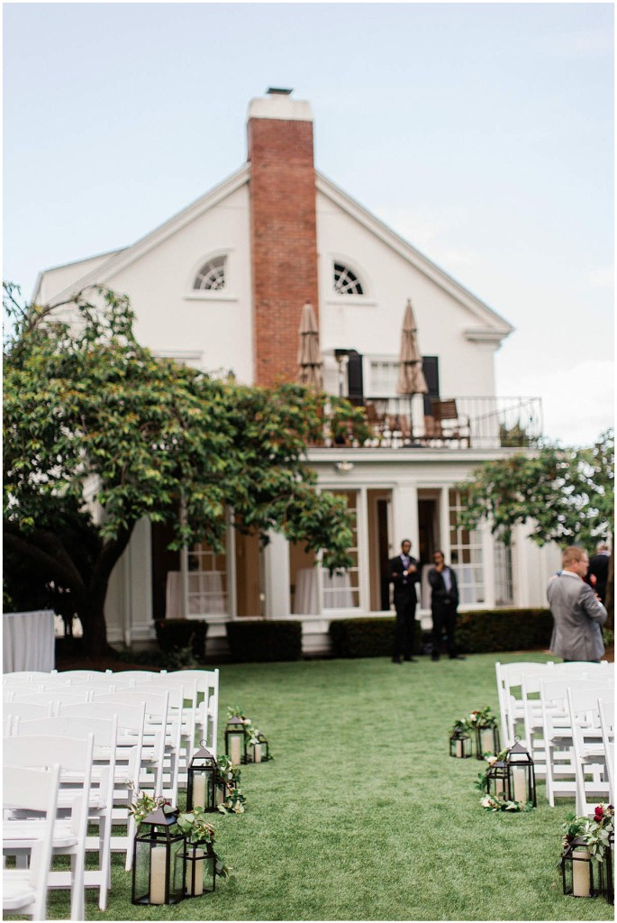 White chairs set up for an outdoor wedding ceremony accessorized with iron lanterns outside of traditional white home, Admiral
