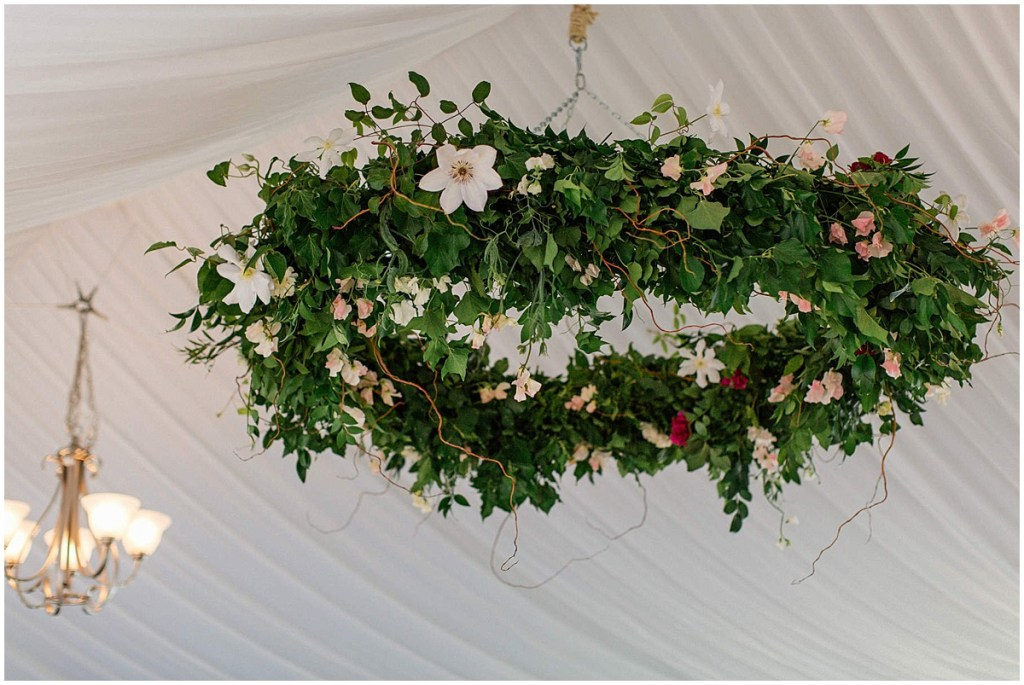 Large, round floral installation hanging from white tent ceiling decorated with greenery and ivory and blush florals, Admiral