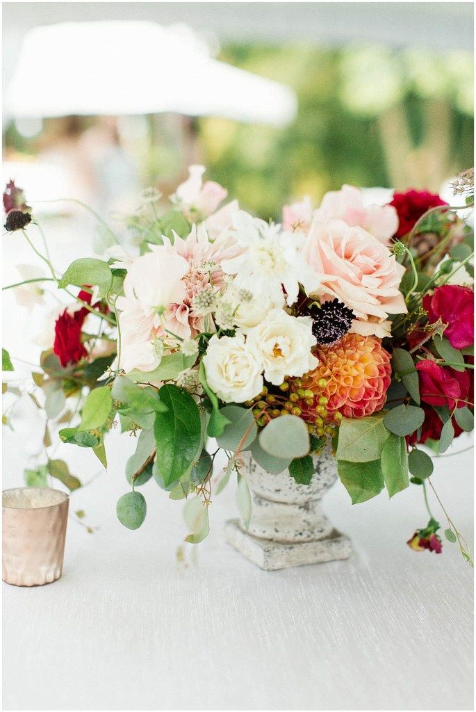 Wedding table centerpiece in a cement urn overflowing with blush, ivory, and burgundy flowers with pops of greenery, Admiral