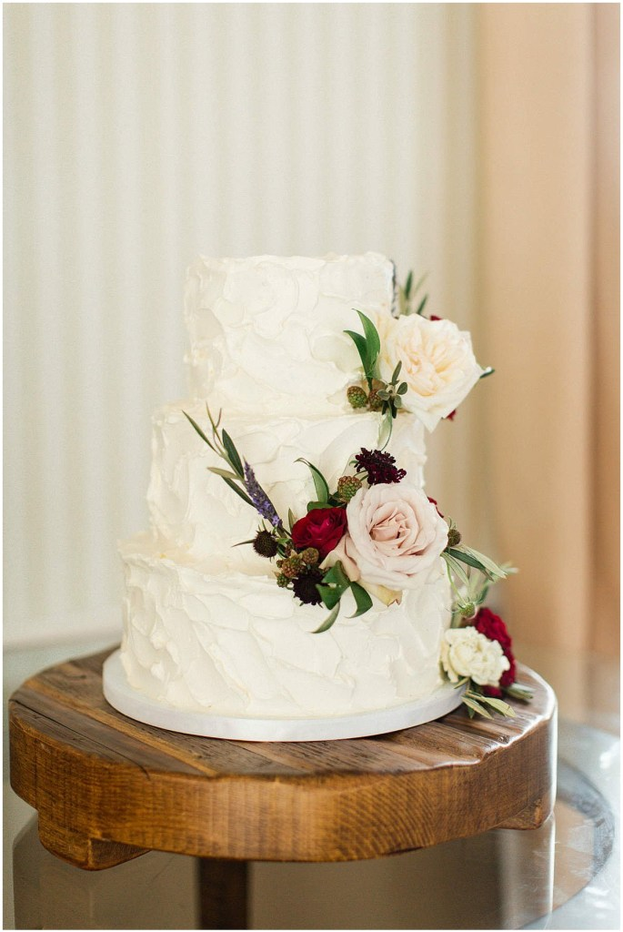 Three tier wedding cake with white frosting decorated with blush, burgundy, and purple flowers, Admiral