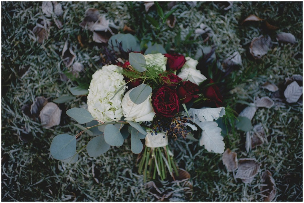 A bridal bouquet made of ivory and deep red flowers lays on grass covered in winter frost, New Years Eve wedding, Cedarbrook Lodge wedding, Seattle wedding, Perfectly Posh Events wedding planning, Washington wedding planner, Photo by Carly Bish