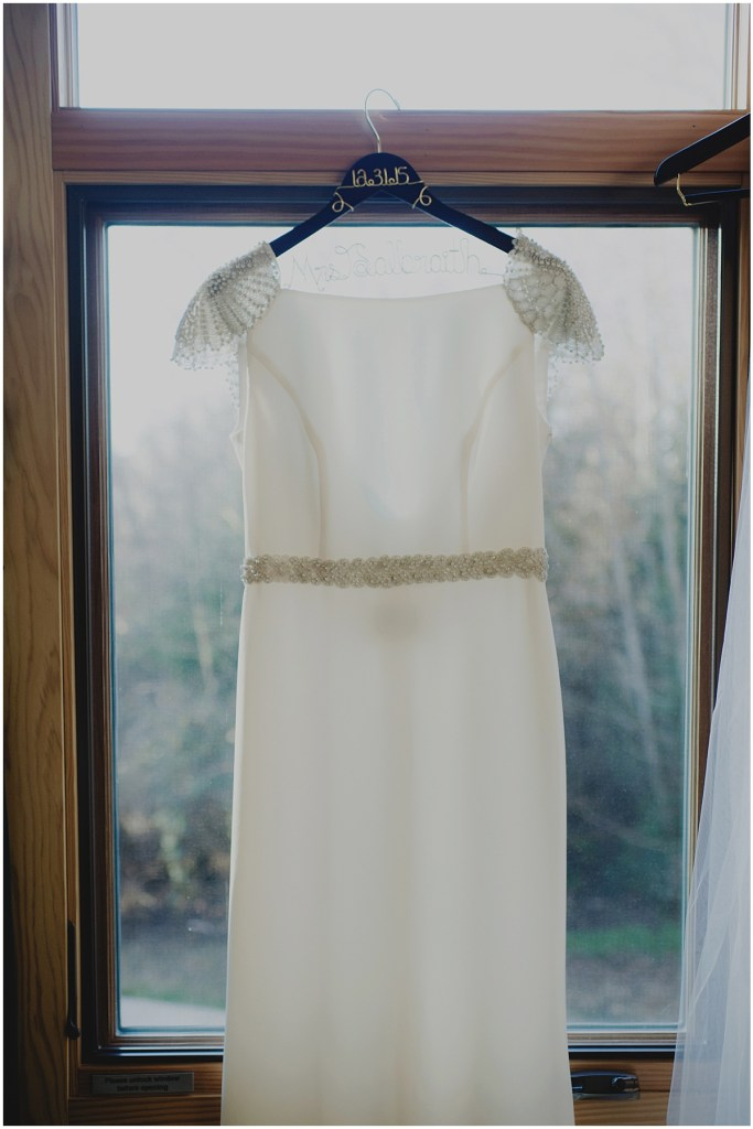 An ivory bridal gown with beaded shoulders and waist hangs in front of a window, New Years Eve wedding, Cedarbrook Lodge wedding, Seattle wedding, Perfectly Posh Events wedding planning, Washington wedding planner, Photo by Carly Bish
