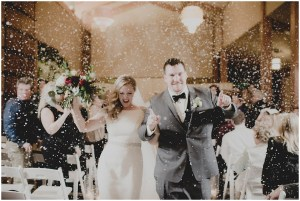 Bride and groom celebrate walking back down aisle after exchanging vows while faux snow falls on them from the ceiling, Cedarbrook Lodge wedding, Seattle wedding, Perfectly Posh Events wedding planning, Washington wedding planner, Photo by Carly Bish