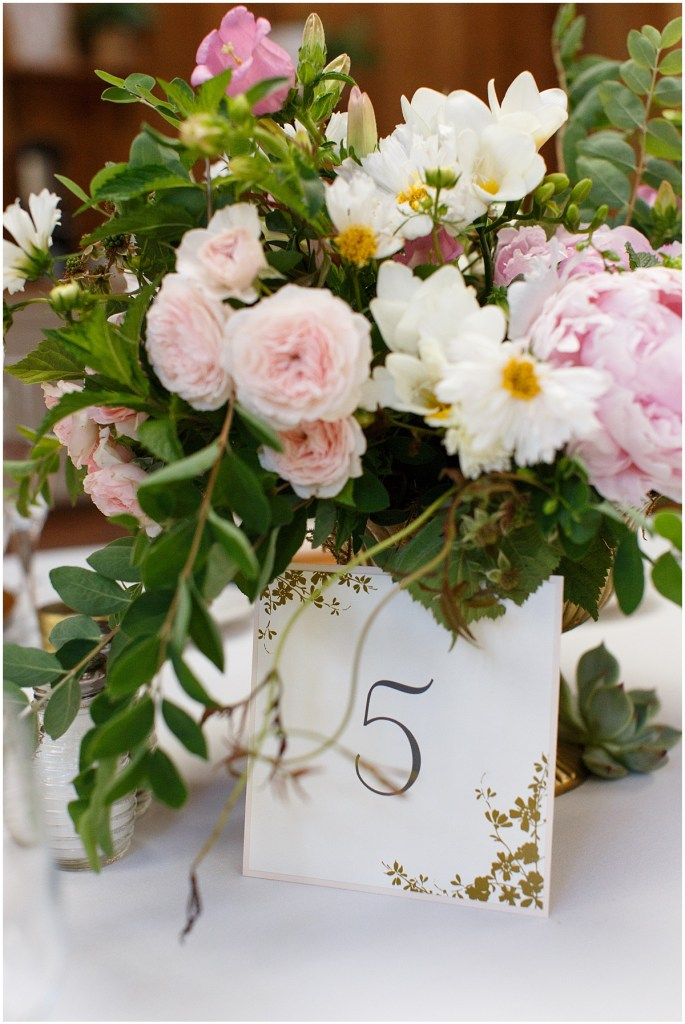 Custom wedding table number with a pink and ivory floral centerpiece with touches of greenery, Kiana Lodge wedding, Perfectly Posh Events wedding planning, Seattle wedding planning, Photo by Amy Soper Photography