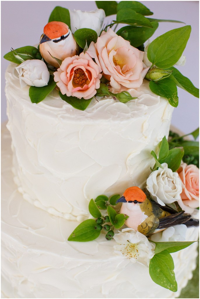 Two tier wedding cake with buttercream frosting decorated with coral and ivory flowers and touches of greenery, Kiana Lodge wedding, Perfectly Posh Events wedding planning, Seattle wedding planning, Photo by Amy Soper Photography