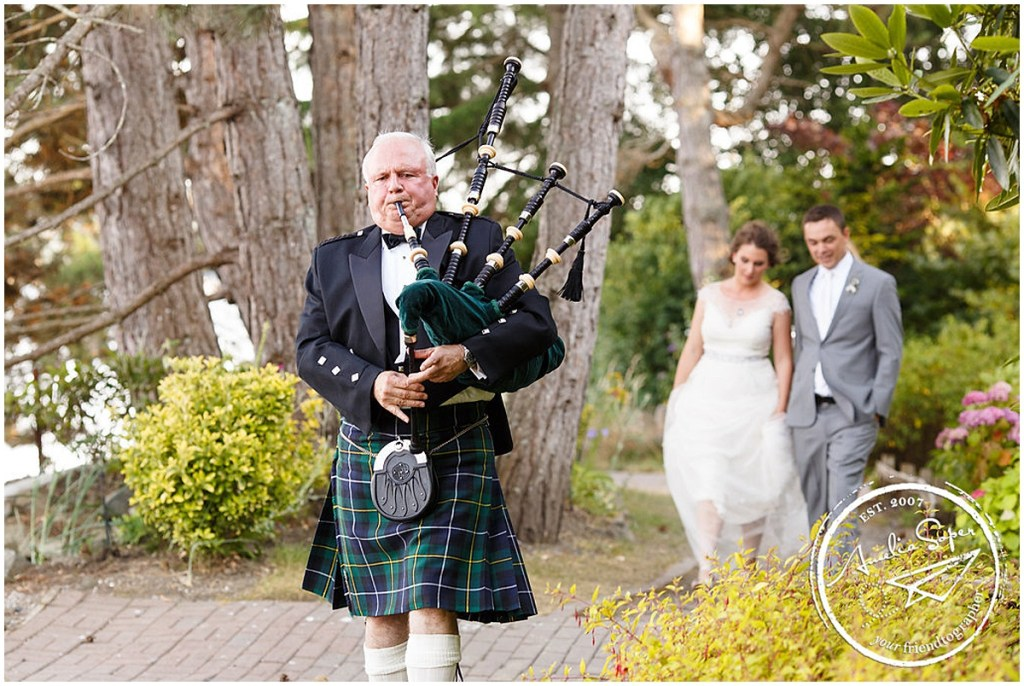 Man wearing traditional Scottish kilt plays bagpipe while bride and groom walk behind him, Kiana Lodge wedding, Perfectly Posh Events wedding planning, Seattle wedding planning, Photo by Amy Soper Photography