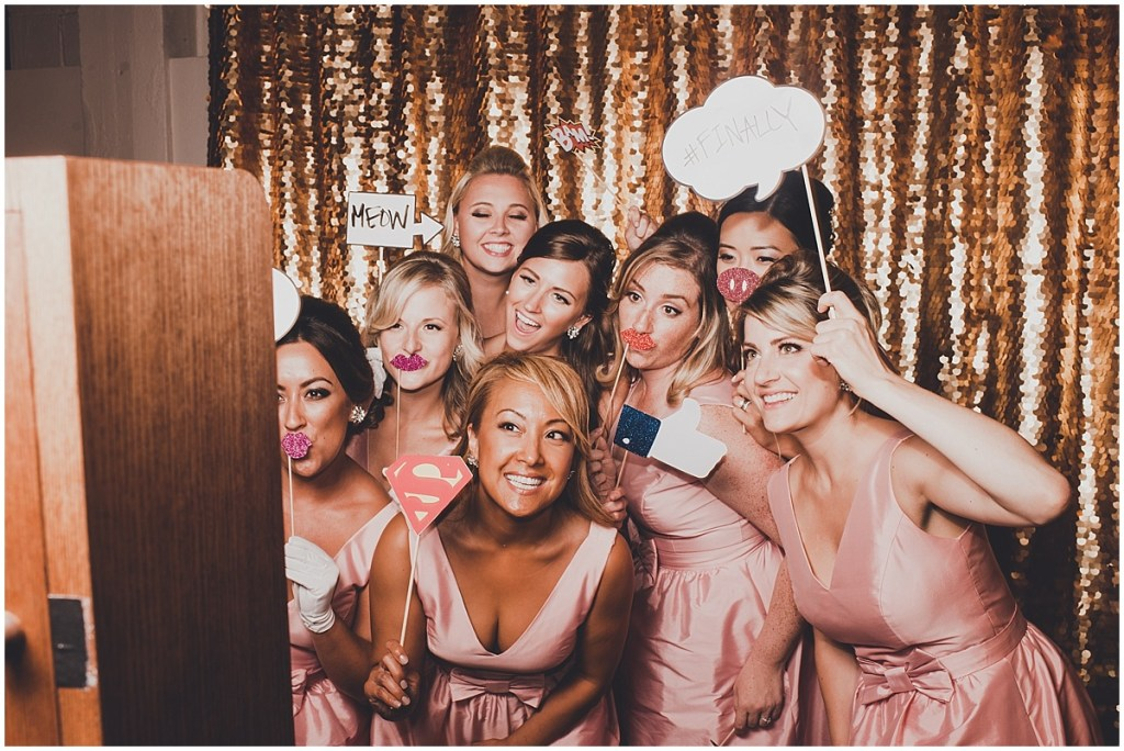 Bridesmaids in light pink gowns hold funny props while posing in a photo booth with a gold sequined curtain, mid century modern wedding, The Foundry by Herban Feast wedding, Seattle wedding, Perfectly Posh Events wedding planning and coordination, Photo by Carina Skrobecki