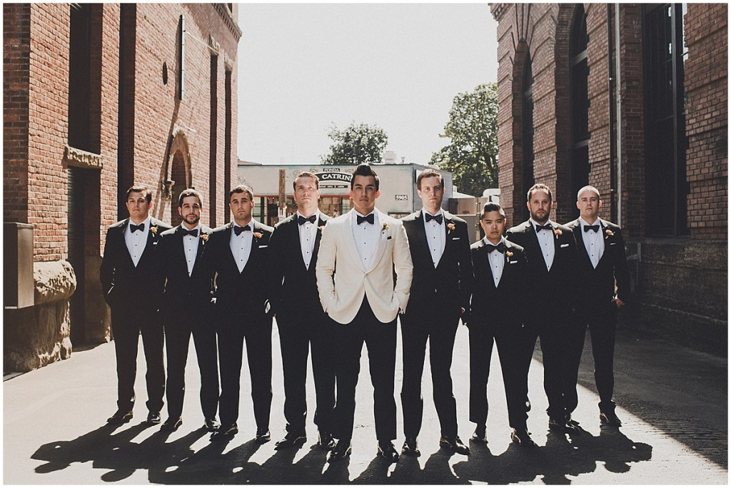 Groom in an ivory tuxedo poses with his groomsmen in between two brick buildings, mid century modern wedding, The Foundry by Herban Feast wedding, Seattle wedding, Perfectly Posh Events wedding planning and coordination, Photo by Carina Skrobecki