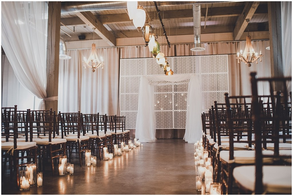 Indoor wedding ceremony set up with dark wooden chairs, vintage glass lamps, white fabric, and a white breeze way backdrop, mid century modern wedding, The Foundry by Herban Feast wedding, Seattle wedding, Perfectly Posh Events wedding planning and coordination, Photo by Carina Skrobecki