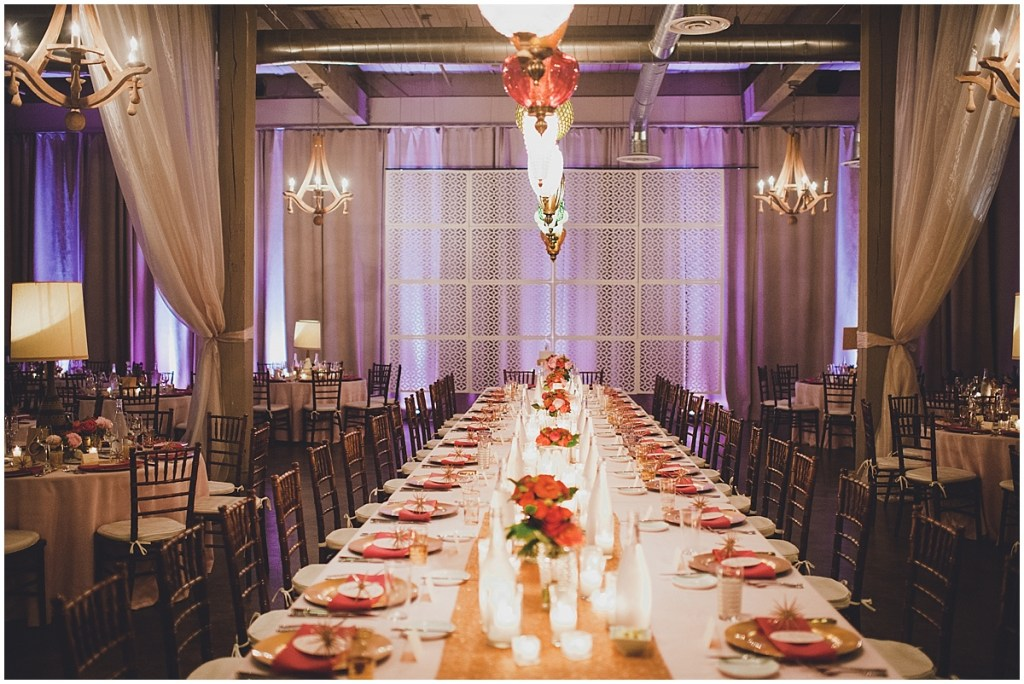 A long wedding reception table decorated with a gold plates, red napkins, gold table runner, and pink floral centerpieces, Mid Century modern wedding,The Foundry by Herban Feast wedding, Seattle wedding, Perfectly Posh Events wedding planning and coordination, Photo by Carina Skrobecki