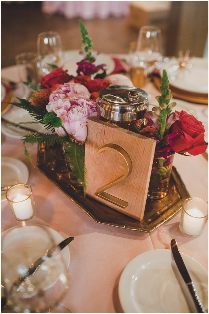 A gold table number on a wood frame sits on a gold tray with pink peonies, Mid Century modern wedding,The Foundry by Herban Feast wedding, Seattle wedding, Perfectly Posh Events wedding planning and coordination, Photo by Carina Skrobecki