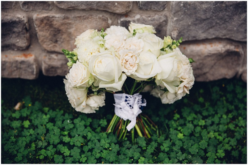 Close up of a bride's ivory floral wedding bouquet sitting amongst a pile of clover, Washington wedding, Perfectly Posh Events wedding planning, Washington wedding planning and coordination, Photo by Mike Fiechtner Photography