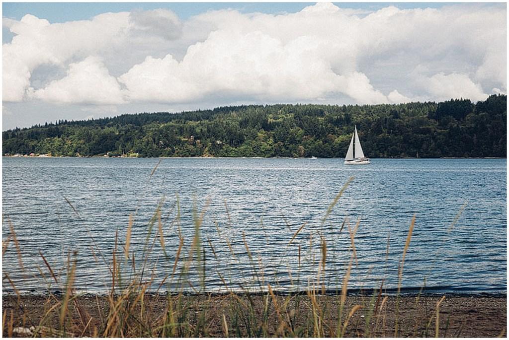 A white sail boat sails through Puget Sound in Gig Harbor, Washington on a bright summer day, Washington wedding, Perfectly Posh Events wedding planning, Washington wedding planner, Photo by Mike Fiechtner Photography