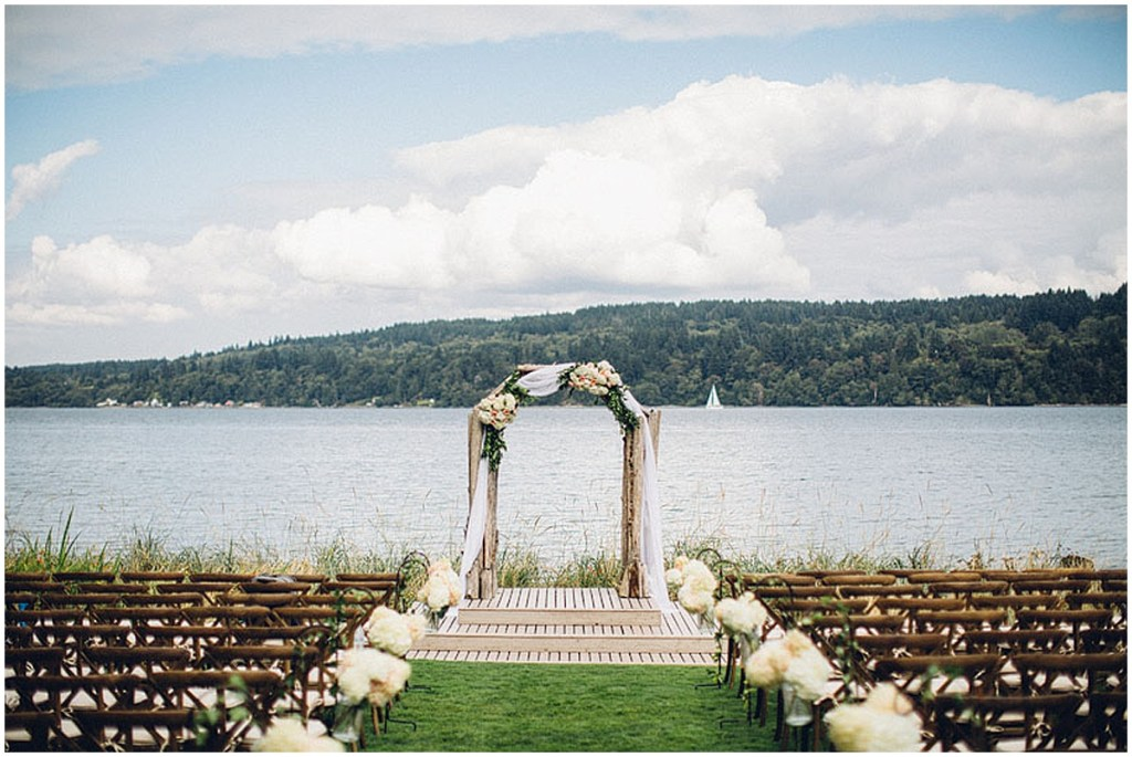 An outdoor waterfront wedding ceremony setup featuring rustic wood chairs and an altar draped in white fabric and covered in ivory and blush florals with touches of greenery, Washington wedding, Perfectly Posh Events wedding planning, Washington wedding planner, Photo by Mike Fiechtner Photography