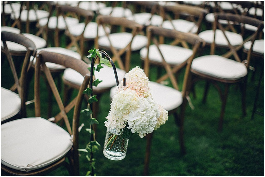 Close up of small vase of white flowers hung from vine covered hook at an outdoor wedding reception with rustic wooden chairs, Washington wedding, Perfectly Posh Events wedding planning, Washington wedding planner, Photo by Mike Fiechtner Photography