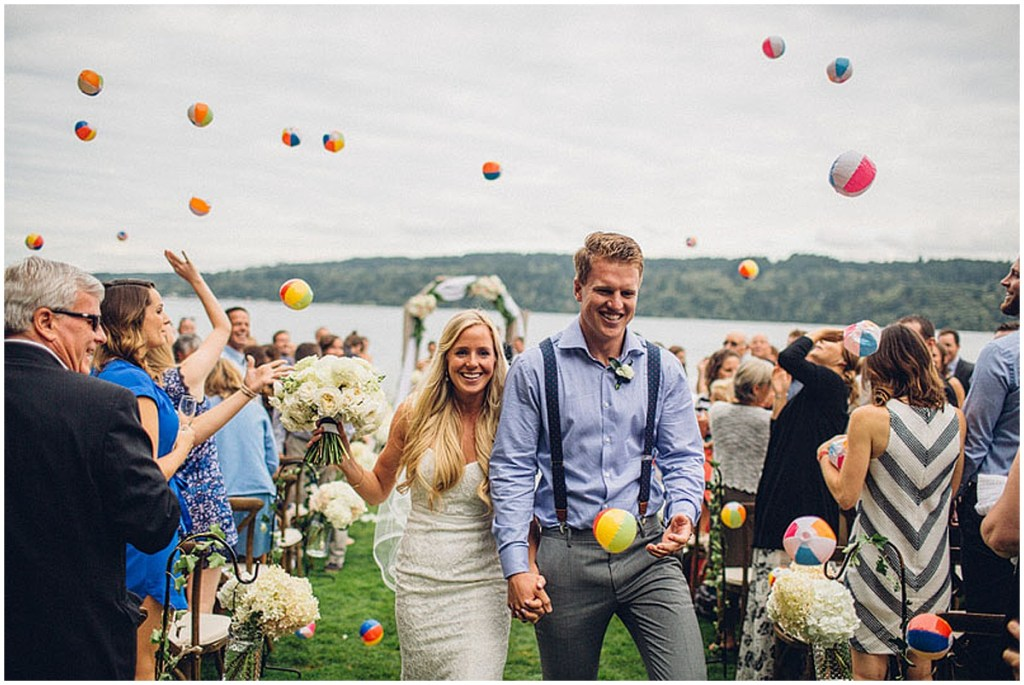 Family and friends use mini beach balls to celebrate a newly married couple walking back down the aisle after exchanging vows, Washington wedding, Perfectly Posh Events wedding planning, Washington wedding planner, Photo by Mike Fiechtner Photography