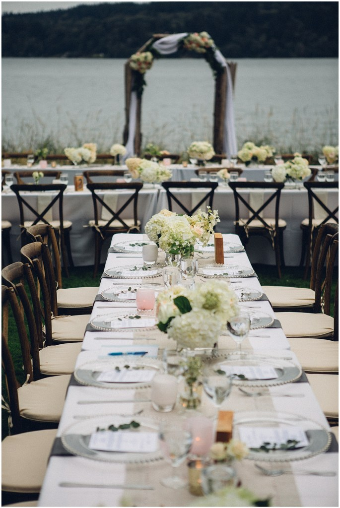 Long wedding dinner tables set up with white table cloths and ivory floral centerpieces at an outdoor waterfront wedding, Washington wedding, Perfectly Posh Events wedding planning, Seattle Wedding Coordinator, Photo by Mike Fiechtner Photography