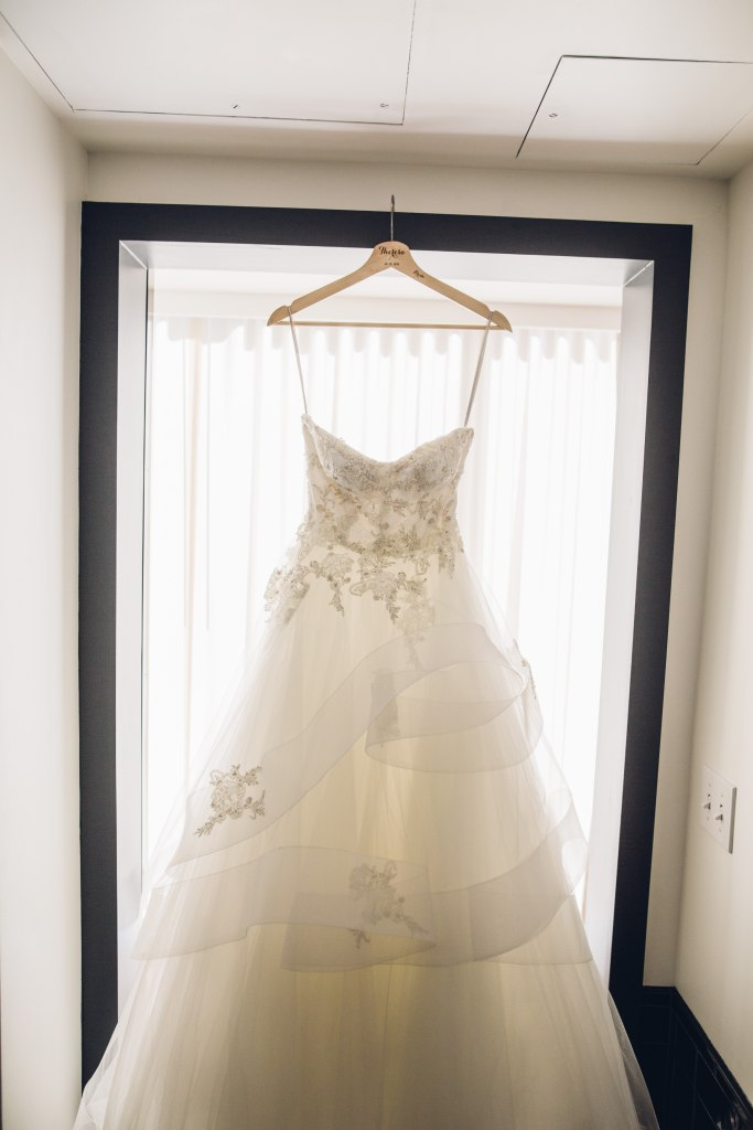 A light ivory ballgown-style wedding dress hangs in front of a window, Italian inspired wedding, Bell Harbor at Pier 66 wedding, Seattle wedding, planning by Perfectly Posh Events, Seattle wedding planner, Photo by Mike Fiechtner Photography