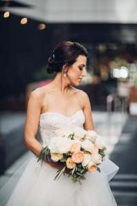 A bride poses with a large bouquet of ivory and coral flowers with touches of greenery, Italian inspired wedding, Bell Harbor at Pier 66 wedding, Seattle wedding, planning by Perfectly Posh Events, Seattle wedding planner, Photo by Mike Fiechtner Photography