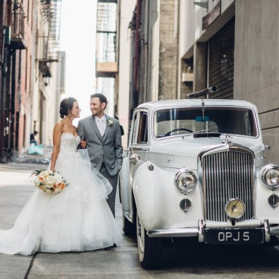 A bride in a white ballgown poses with groom in a grey suit while standing next to a vintage 1950's Bentley, Italian inspired wedding, Bell Harbor at Pier 66 wedding, Seattle wedding, planning by Perfectly Posh Events, Seattle wedding planner, Photo by Mike Fiechtner Photography