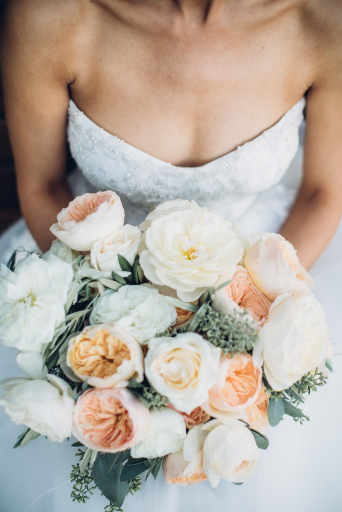 Close up of a bride holding an ivory and coral colored floral bouquet, Italian inspired wedding, Bell Harbor at Pier 66 wedding, Seattle wedding, planning by Perfectly Posh Events, Seattle wedding planner, Photo by Mike Fiechtner Photography