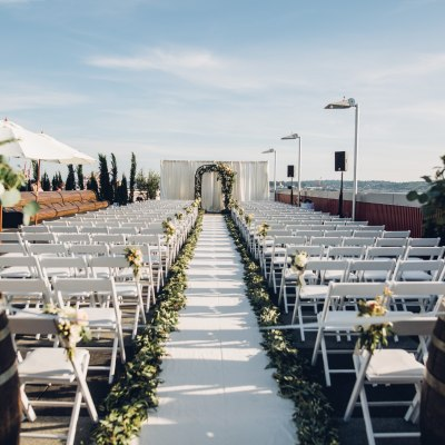 A wedding ceremony is set up on a rooftop by Seattle's waterfront with white chairs and a floral altar, Italian inspired wedding, Bell Harbor at Pier 66 wedding, Seattle wedding, planning by Perfectly Posh Events, Seattle wedding planner, Photo by Mike Fiechtner Photography