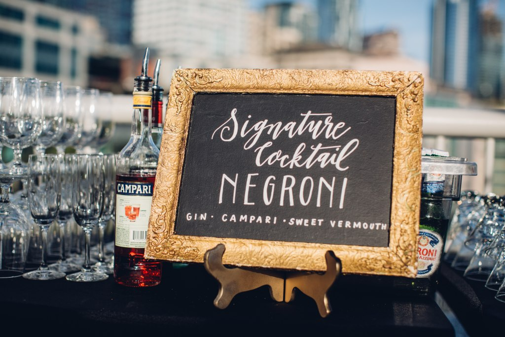 A signature cocktail sign featuring Negroni is hand drawn onto chalk board sitting atop a bar, Italian inspired wedding, Bell Harbor at Pier 66 wedding, Seattle wedding, planning by Perfectly Posh Events, Seattle wedding planner, Photo by Mike Fiechtner Photography