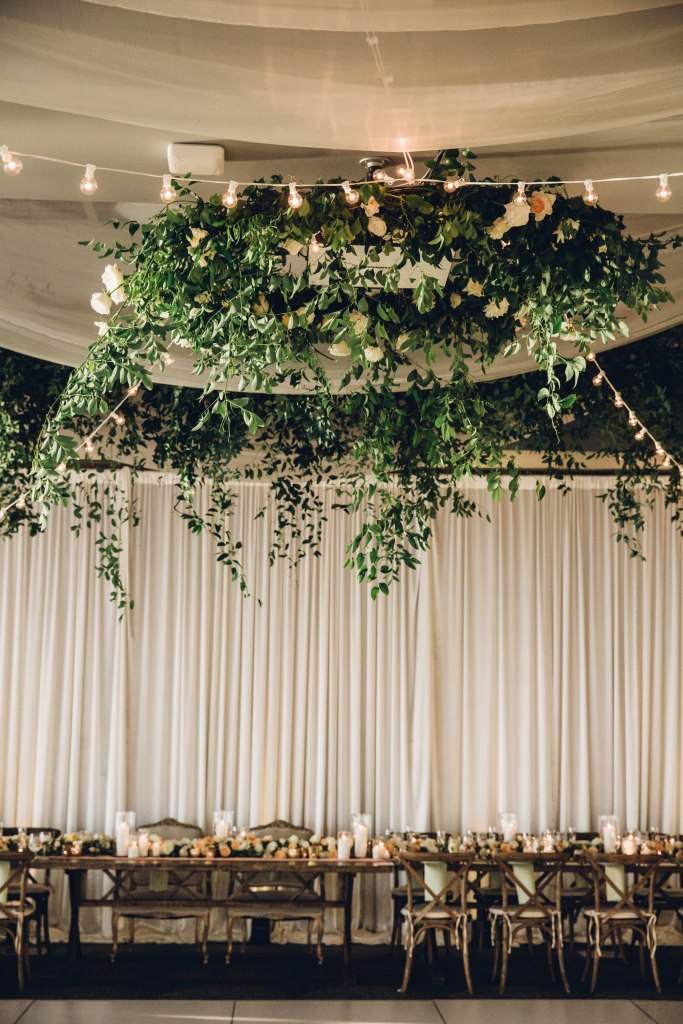 A large greenery and floral display hangs from the ceiling in the middle of a wedding reception, Italian inspired wedding, Bell Harbor at Pier 66 wedding, Seattle wedding, planning by Perfectly Posh Events, Seattle wedding planner, Photo by Mike Fiechtner Photography