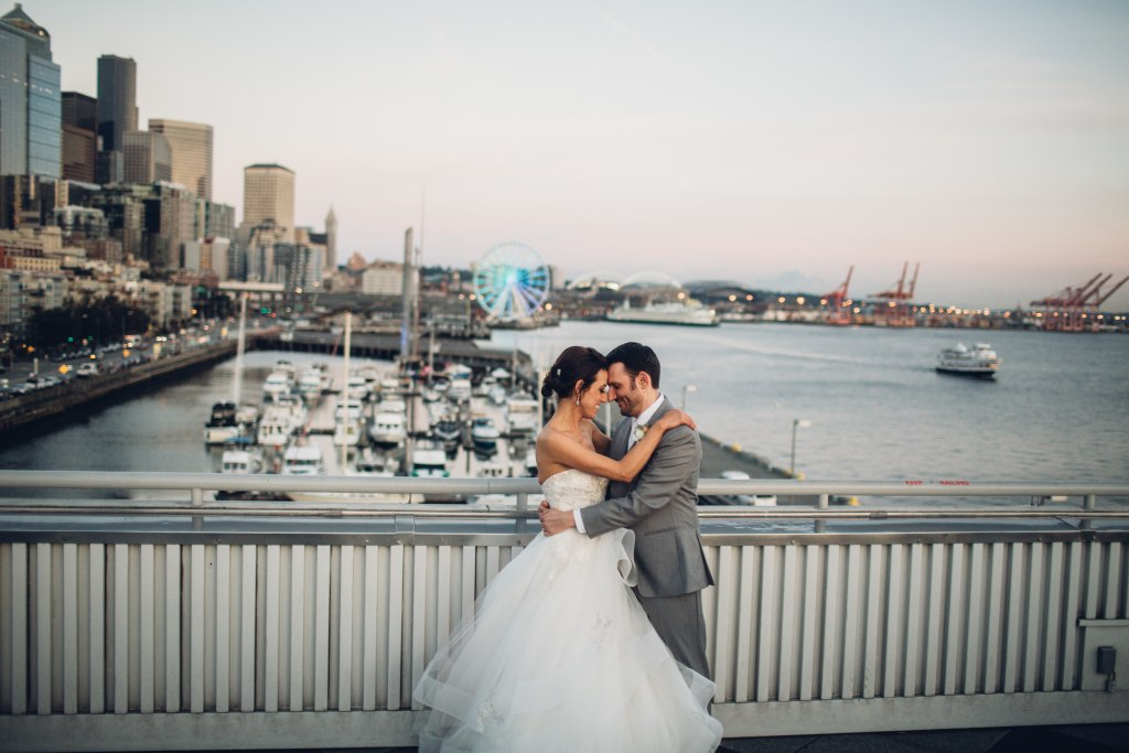 Bride and groom embrace each other with a view of Downtown Seattle in the background, Seattle Great Wheel, Bell Harbor at Pier 66 wedding, Seattle wedding, planning by Perfectly Posh Events, Seattle wedding planner, Photo by Mike Fiechtner Photography