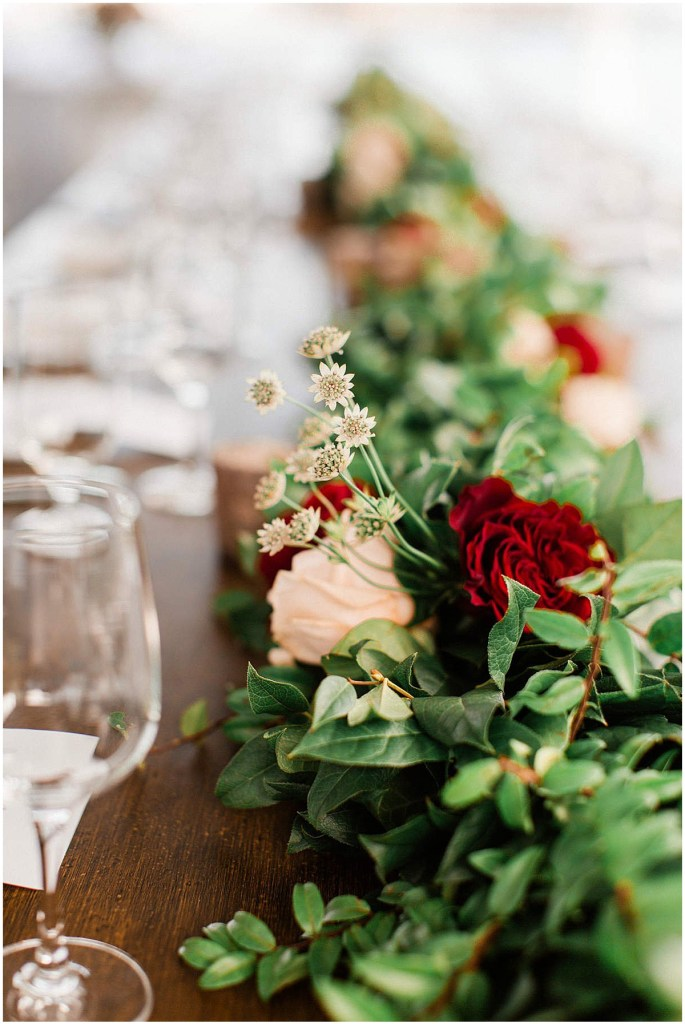 Close up of long table centerpiece of greenery featuring pops of red and blush flowers on a rustic wood table, Admiral